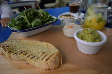 Hummus, guacamole, pao de cereais, frutas naturais, ovo poché e salada de rúcula